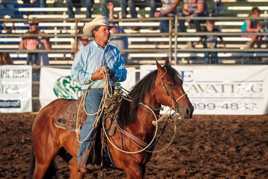 Cowboy at a rodeo sits on his horse after attempting to rope a calf
