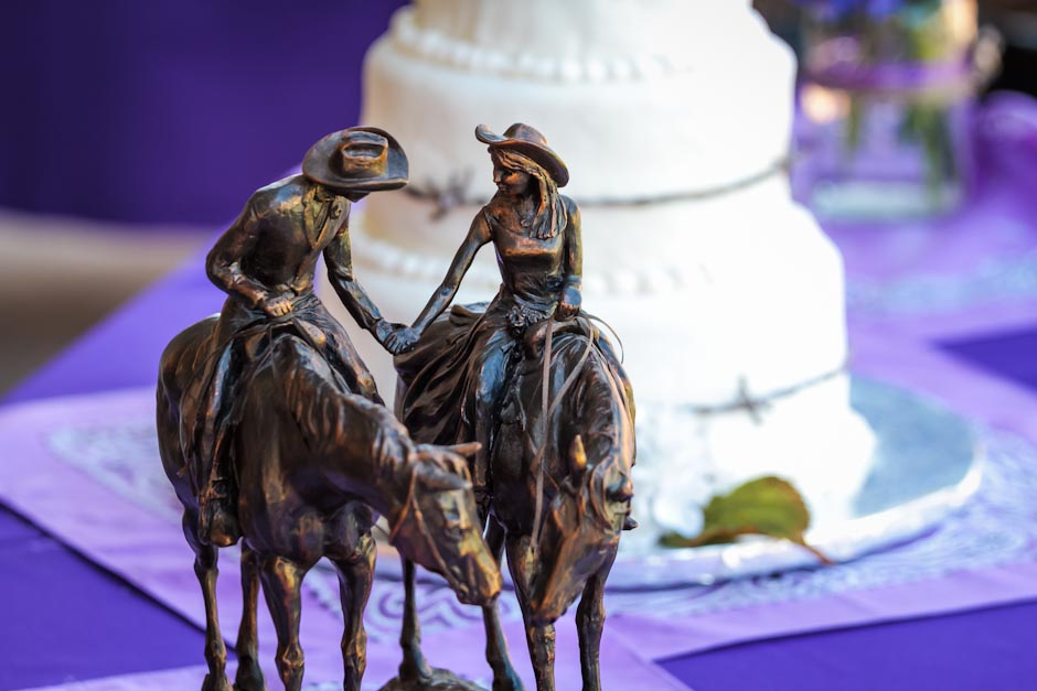 Statue of man and woman riding horses in front of wedding cake