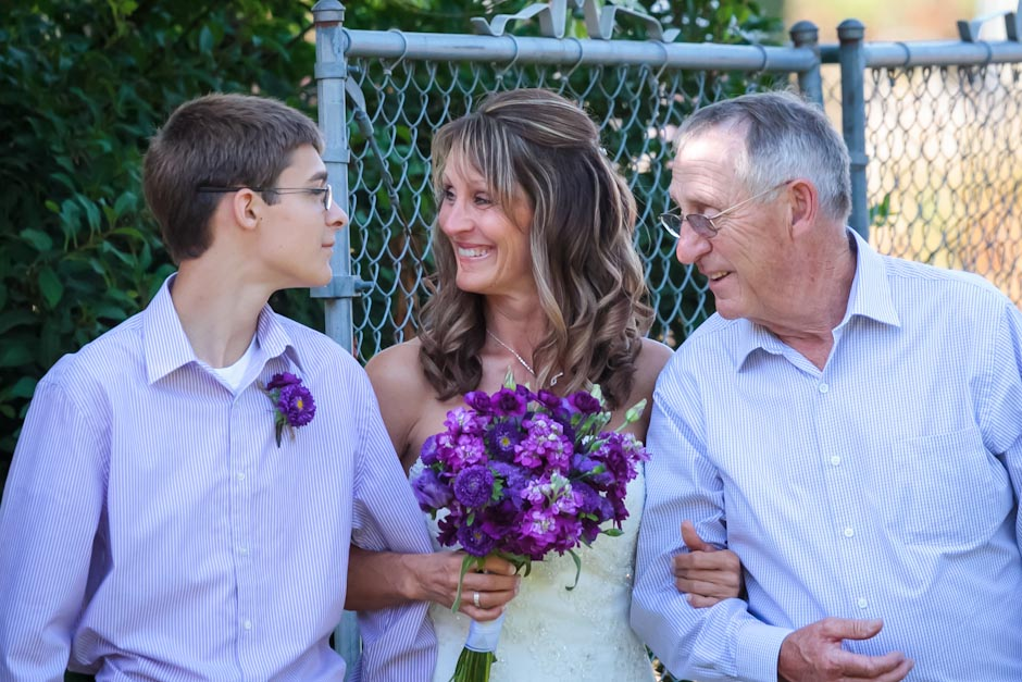 Bride walks down the aisle with her dad and son who will give her away